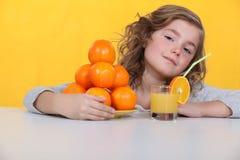 Young girl drinking orange juice stock image