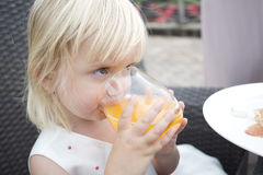 Young girl drinking orange juice outside in garden Royalty Free Stock Images