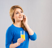 Young girl drinking orange juice and talking on a phone Stock Photo