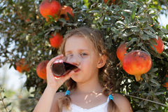 Young girl drinking pomegranate juice Stock Photo