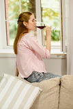 Young girl drinking red wine. Stock Images