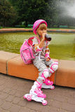 Young girl drinking and  rollerskating. Young girl in pink helmet drinking juice Stock Images