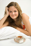 Young girl drinking tea in bed Royalty Free Stock Images