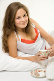Young girl drinking tea in bed Royalty Free Stock Photo