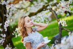 Young girl drinking tea in cherry garden stock photo