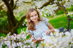 Young girl drinking tea in cherry garden Stock Images