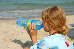 Young girl drinking water on the beach Stock Images