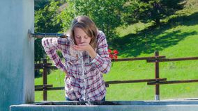 Young girl drinking from a water fountain stock footage