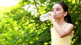 Young girl drinking water. Out of a plastic bottle stock video