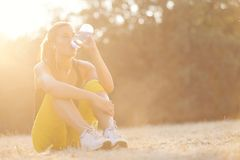 Young girl drinking water after workout. Beautiful girl resting after hard workout while listening to the music Royalty Free Stock Photo