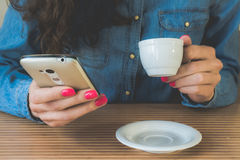 Young girl drinks coffee and enjoys the phone in a cafe. Young girl in a denim shirt sitting in the cafe at the wooden table. In her hands with a red manicure Stock Photos