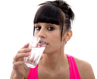Young girl drinks a glass of water, on white Stock Photography