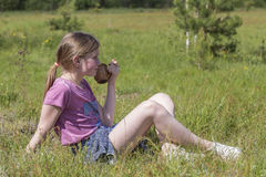 Young girl drinks juice sitting on green grass. Stock Photo