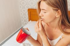 The girl drinks a pill from the disease, drinking her glass of w stock photo