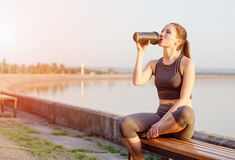 Young girl drinks a protein cocktail from a schweeter after jogging. Young girl of Caucasian appearance drinks a protein cocktail from a shaker after jogging in royalty free stock image