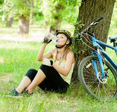 Young girl drinks water from a bottle after mountain biking Royalty Free Stock Photos