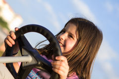 Learning to drive. A beautiful young girl having fun learning how to drive in a beautiful sunny day Stock Photography