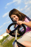 Learning to drive. A beautiful young girl having fun learning how to drive in a sunny day Royalty Free Stock Image