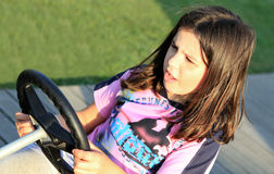 Learning to drive. A beautiful young girl having fun learning how to drive in a sunny day Royalty Free Stock Images