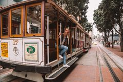 Young girl driving on the cable car in San Francisco. By the very edge of the cabin stock image