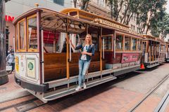Young girl driving on the cable car in San Francisco. By the very edge of the cabin royalty free stock images