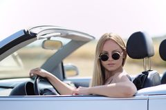 Girl driving a cabriolet in a summer poppy field royalty free stock image