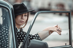 Young girl driving a retro car. By the road at the fields Royalty Free Stock Images