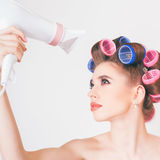 Young girl drying hair by hairdryer Stock Photos
