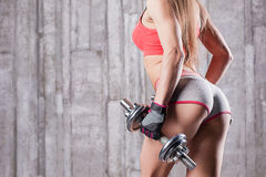 Young girl with dumbbells and taut buttocks. In gym Stock Image
