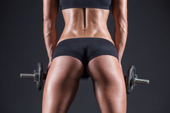 Young girl with dumbbells and taut buttocks Stock Image