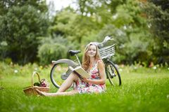 Young girl with eading a book outdoors Royalty Free Stock Images