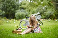 Young girl with eading a book outdoors Royalty Free Stock Photos