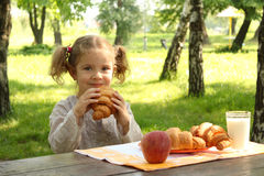 Young girl eat croissant Stock Image