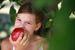 Young girl eating an apple