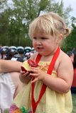 Young girl eating an apple. Young female eating an apple at an outdoor summer event Stock Photography