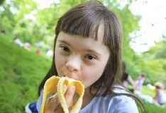 Young girl eating banana in the park royalty free stock photos