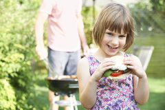 Young Girl Eating Beefburger At Family Barbeque Stock Image