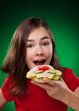 Young girl eating big sandwich Royalty Free Stock Photos