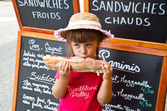 Young girl eating a big sandwich Royalty Free Stock Images