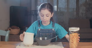 Young girl eating a bowl of cereals. Child nutrition - Young girl eating a bowl of cereals stock video footage