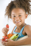 Young girl eating bowl of vegetables in living roo