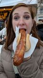 Girl eating a bratwurst sausage. Young girl eating a bratwurst sausage in Germany at a street market Stock Photo