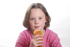 Young girl eating a bun Stock Photo