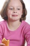 Young girl eating a bun Royalty Free Stock Photos