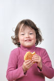 Young girl eating a bun Stock Image