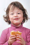 Young girl eating a bun Royalty Free Stock Photography