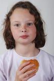 Young girl eating a bun Royalty Free Stock Photography