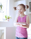 Young girl eating cake in kitchen Royalty Free Stock Photography