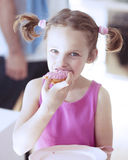 Young girl eating cake in kitchen Royalty Free Stock Photos
