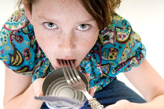 Young girl eating from can. Young girl eating food straight from can Stock Photo